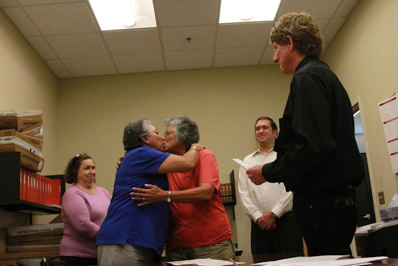 Catherine Martinez and Linda Montoya kiss as Dona Ana County employee and Reverend Jess C. Williams marries them at the Dona Ana County Clerk's Office in Las Cruces, New Mexico, Wednesday, Aug. 21, 2013. More than 40 same-sex couples obtained their marriage licenses after the county clerk announced the county would be the first in New Mexico to marry same-sex couples. (AP Photo/Juan Carlos Llorca)