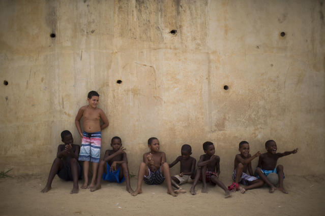 Young residents watch from the sidelines a pickup game of soccer at the Sao Carlos slum in Rio de Janeiro, Brazil, Friday, March 7, 2014. (AP Photo/Felipe Dana)