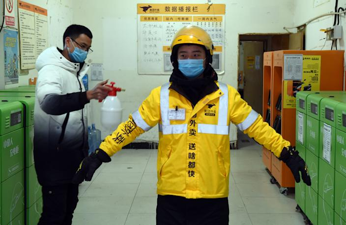 A Meituan food courier being disinfected.