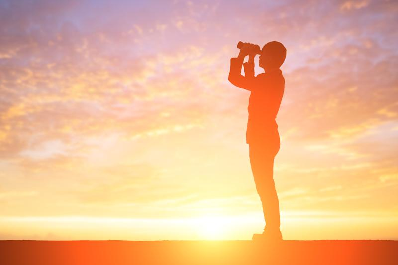 A person looking through binoculars at sunset, silhouetted against a golden sky