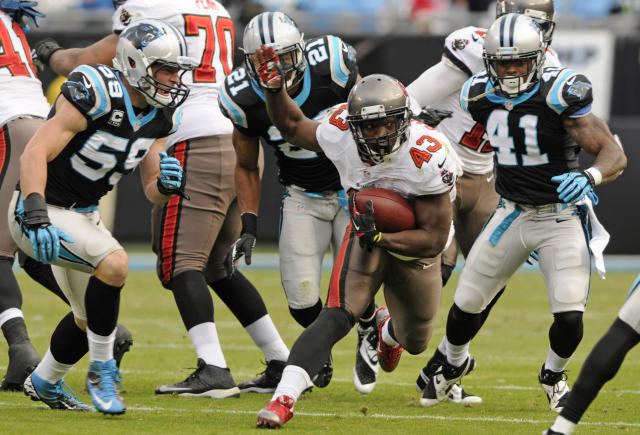 Tampa Bay Buccaneers' Bobby Rainey (43) runs between Carolina Panthers' Luke Kuechly (59) and Captain Munnerlyn (41) in the second half of an NFL football game in Charlotte, N.C., Sunday, Dec. 1, 2013. (AP Photo/Mike McCarn)