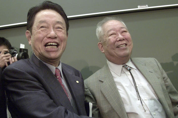 FILE - In this Oct. 8, 2002, file photo, Japanese physicist Masatoshi Koshiba, right, is congratulated by 1973 Nobel Prize winner in Physics Reona Ezaki after Koshiba won the Nobel Prize in Physics in 2002 at the University of Tokyo, in Tokyo. Koshiba, a co-winner of the Nobel Prize for his pioneering researches into the make-up of the universe, died Thursday, Nov. 12, 2020, the university said. He was 94. (AP Photo/Junji Kurokawa, File)