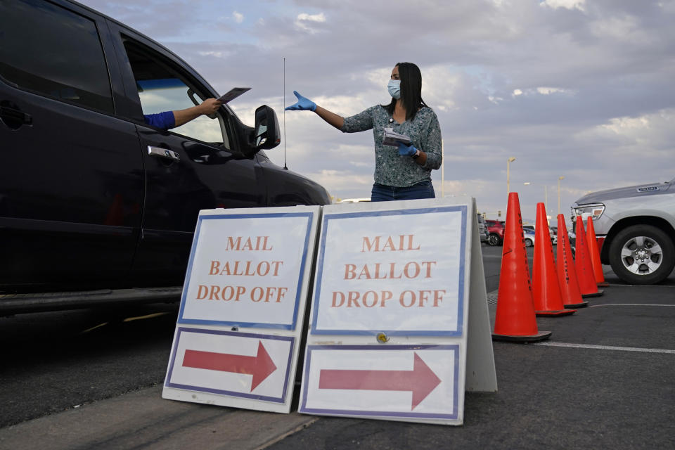 FILE - In this Nov. 2, 2020, file photo, a county worker collects mail-in ballots in a drive-thru mail-in ballot drop off area at the Clark County Election Department in Las Vegas. A state court legal fight to stop the counting of mail ballots in the Las Vegas area has ended after the Nevada Supreme Court Tuesday, Nov. 10, dismissed an appeal by the Donald Trump campaign and the state Republican party, at their request. The dismissal leaves two active legal cases in Nevada relating to the 2020 presidential election, as a small number of remaining ballots are counted. (AP Photo/John Locher, File)