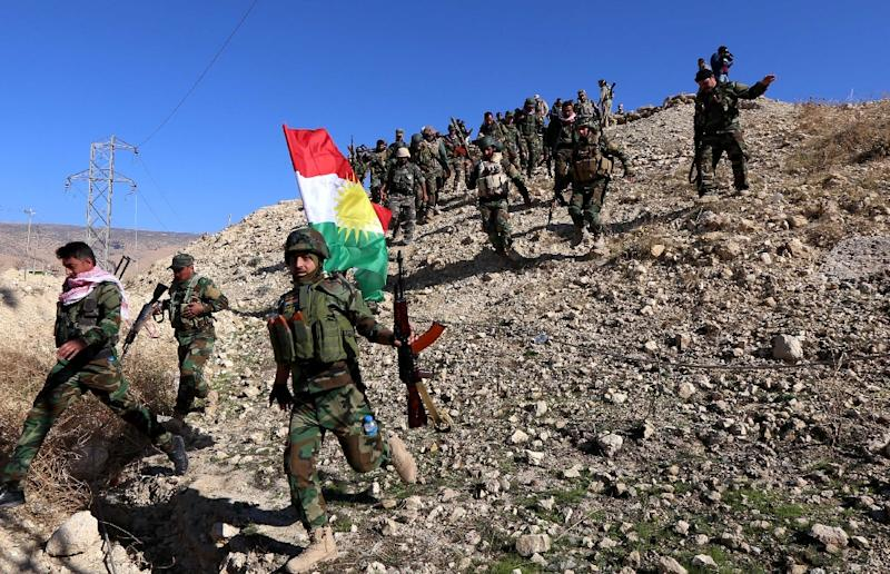 Iraqi autonomous Kurdish region's peshmerga forces and fighters from the Yazidi minority hold a Kurdish flag while entering the northern Iraqi town of Sinjar, in the Nineveh Province, on November 13, 2015 (AFP Photo/Safin Hamed)