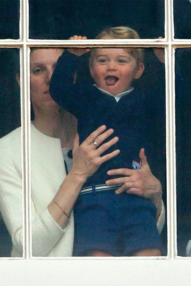 <p>Prince George of Cambridge peeks outside the windows of Buckingham Palace to watch the Trooping the Colour.</p>