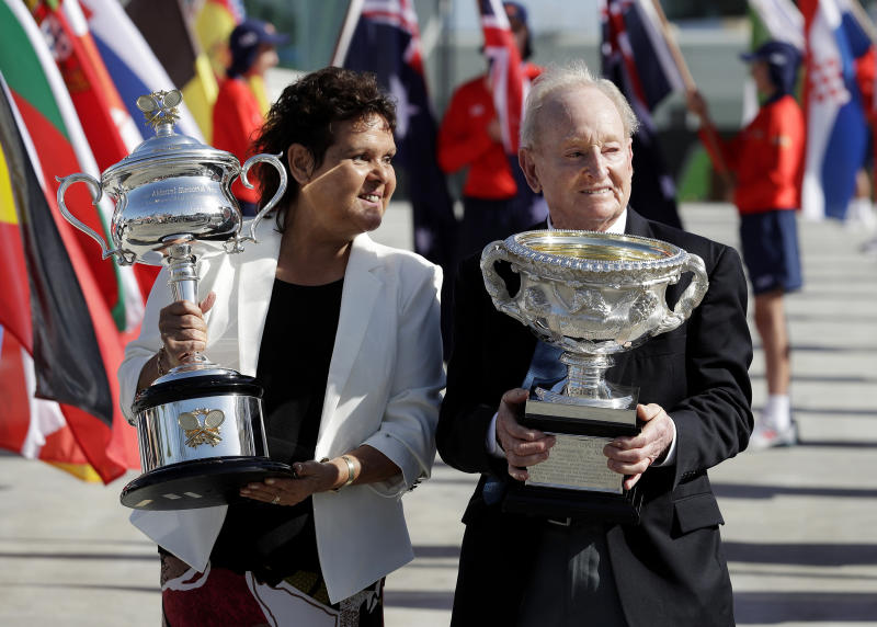 """FILE - In this Jan. 14, 2019, file photo, Australian tennis legends Evonne Goolagong Cawley and Rod Laver hold the women's and men's trophies, the Daphne Akhurst Memorial Cup and the Norman Brookes Challenge Cup at the official start of the Australian Open tennis championships in Melbourne, Australia. Goolagong Cawley says fellow indigenous athlete Ashleigh Barty's first Grand Slam singles title at the French Open was """"a joy to watch."""" (AP Photo/Aaron Favila, File)"""