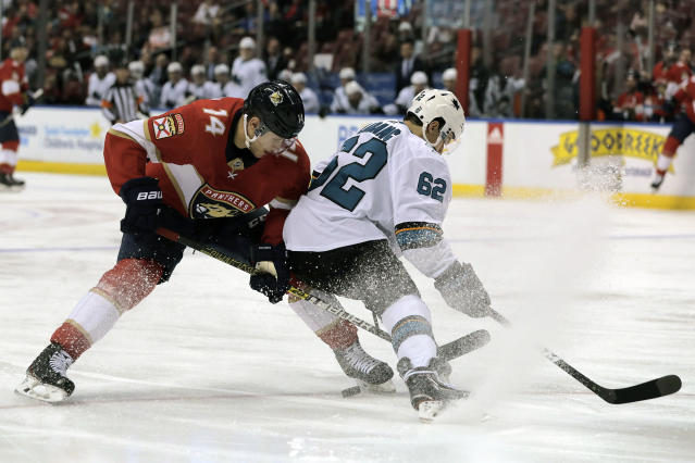 Florida Panthers' Dominic Toninato (14) and San Jose Sharks' Kevin Labanc (62) battle for the puck during the second period of an NHL hockey game, Sunday, Dec. 8, 2019, in Sunrise, Fla. (AP Photo/Luis M. Alvarez)