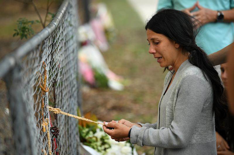 The victims' mother Leila Abdallah pauses near flowers placed at the scene where seven children were hit on a footpath by a four-wheel drive in the Sydney suburb of Oatlands.
