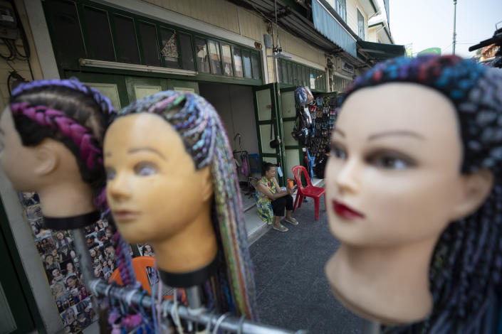 A lone hairdresser wait for customers in Khao San road, a popular hangout for Thais and tourists in Bangkok, Thailand, Wednesday, Feb. 3, 2021. Amid fears of new variants of the virus, new restrictions on movement have hit just as people start to look ahead to what is usually a busy time of year for travel. (AP Photo/Sakchai Lalit)