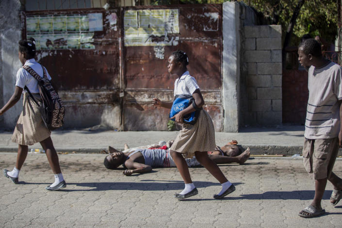 Students rush past the bodies of inmates outside the Croix-des-Bouquets Civil Prison after an attempted breakout, in Port-au-Prince, Haiti, Thursday, Feb. 25, 2021. At least seven people were killed and one injured on Thursday after eyewitnesses told The Associated Press that several inmates tried to escape from a prison in Haiti's capital. (AP Photo/Dieu Nalio Chery).