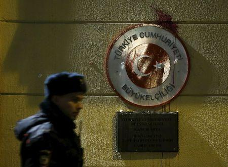 Policeman walks past sign of Turkish embassy stained by protesters in reaction after Russian war plane was shot down by Turkey in Moscow