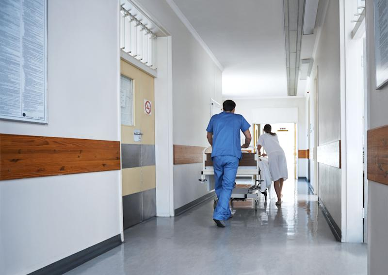Rearview shot of hospital staff wheeling a patient in a gurney down a corridor (Photo: shapecharge via Getty Images)
