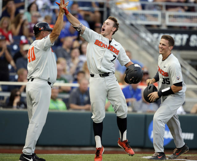 Oregon State's Tyler Malone (7) celebrates with Adley Rutschman (35) and Michael Attalah (40) after hitting a three-run home run against Mississippi State in the third inning of an NCAA College World Series baseball elimination game in Omaha, Neb., Saturday, June 23, 2018. (AP Photo/Nati Harnik)