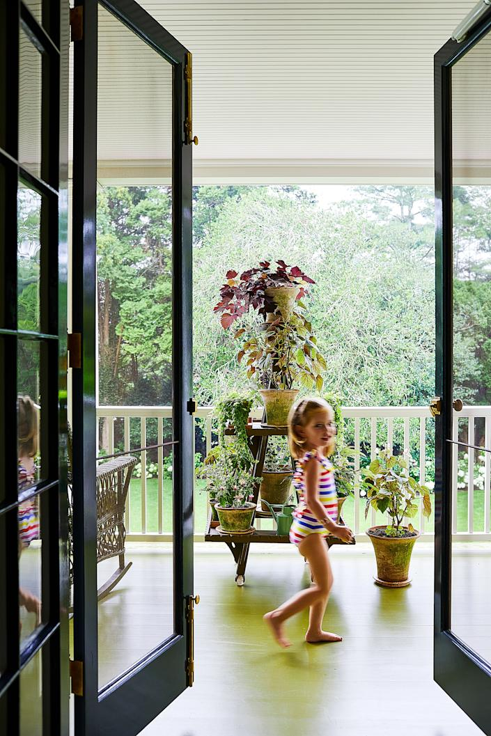 """<div class=""""caption""""> Delphine on the porch. Late–19th century plant stand. </div>"""