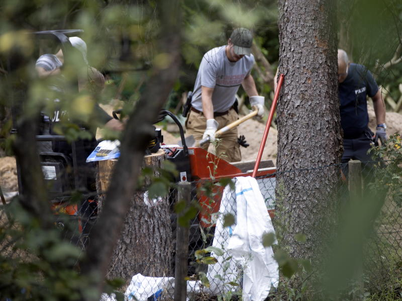 Police officers dig and search the garden plot. Source: AP
