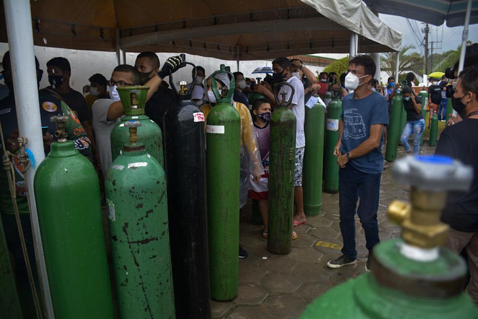 Relatives of patients infected with Covid-19 queue for long hours to refill their oxygen tanks at the Carboxi company in Manaus, Amazonas state, Brazil, on January 19, 2021. - Under an overwhelming heat, dozens of people have been waiting for 12 hours to fill oxygen tanks and try to save the lives of their loved ones in Manaus, a Brazilian city plunged into chaos by the explosion of Covid-19 cases. (Photo by MARCIO JAMES / AFP) (Photo by MARCIO JAMES/AFP via Getty Images)