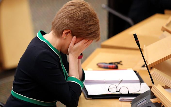 Scotland's First Minister Nicola Sturgeon with her head in hands - RUSSELL CHEYNE/POOL/AFP via Getty Images