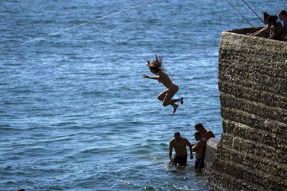 People jump into the sea at Brighton beach in East Sussex (Steve Parsons/PA) (PA Wire)