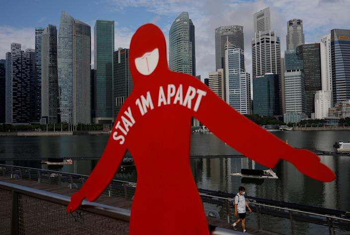 A man wearing a face mask passes a sign put up to encourage social distancing during the coronavirus disease (COVID-19) outbreak, at Marina Bay in Singapore, September 22, 2021. REUTERS/Edgar Su