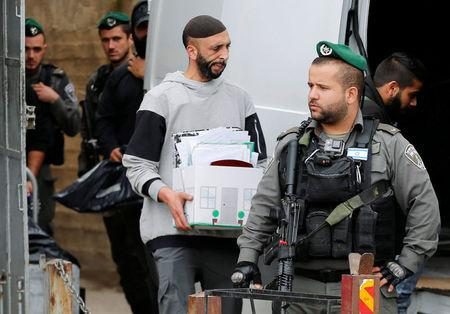An undercover Israeli security officer carries a box containing documents seized from a Palestinian map office by Israeli security officers as they carry out an Israeli police order to close the office, in Arab East Jerusalem neighbourhood of Beit Hanina