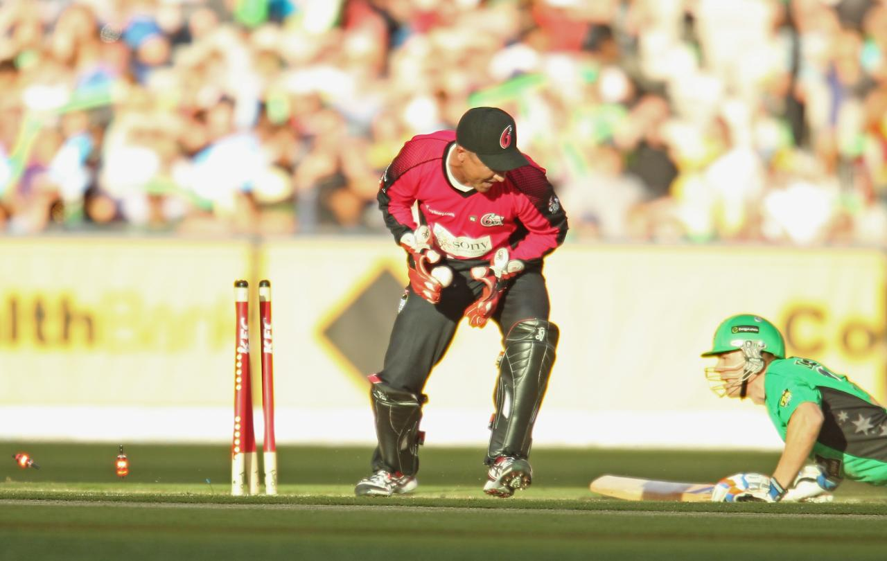 MELBOURNE, AUSTRALIA - DECEMBER 21:  Brad Haddin of the Sixers takes the bails off to run out Scott Henry of the Stars during the Big Bash League match between the Melbourne Stars and the Sydney Sixers at Melbourne Cricket Ground on December 21, 2012 in Melbourne, Australia.  (Photo by Scott Barbour/Getty Images)