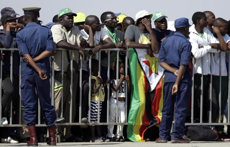 Zimbabweans await for the arrival of the body of Zimbabwe's longtime ruler Robert Mugabe from Singapore, at the Robert Gabriel Mugabe International Airport in HarareHarare, Zimbabwe, Wednesday, Sept. 11, 2019. (AP Photo/Themba Hadebe)