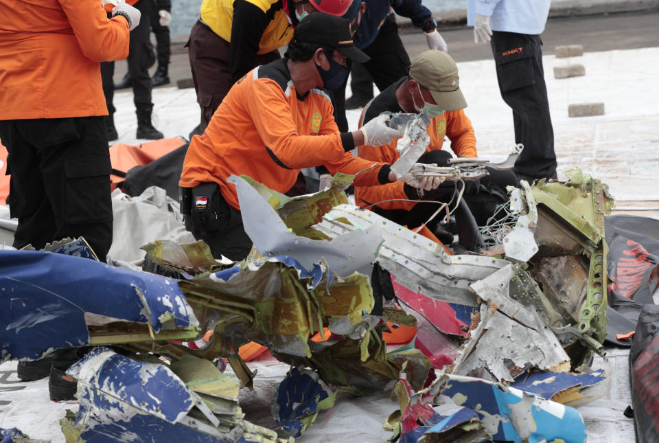 Workers sort parts of aircraft and debris retrieved from from the Java Sea where a Sriwijaya Air jet crashed on Saturday, to be arranged and examined by investigators at Tanjung Priok Port in Jakarta, Indonesia, Thursday, Jan. 14, 2021. An aerial search for victims and wreckage of a crashed Indonesian plane expanded Thursday as divers continued combing the debris-littered seabed looking for the cockpit voice recorder from the lost Sriwijaya Air jet. (AP Photo/Dita Alangkara)