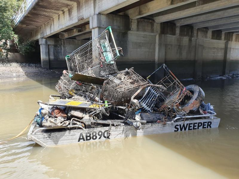 A boat filled with garbage including shopping trolleys floats in Cooks River, Sydney.