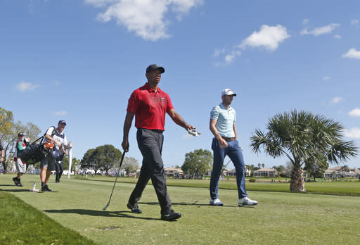 Tiger Woods, center, and Sam Burns, right, walk off the tee on the fifth hole during the final round of the Honda Classic golf tournament, Sunday, Feb. 25, 2018, in Palm Beach Gardens, Fla. (AP Photo/Wilfredo Lee)