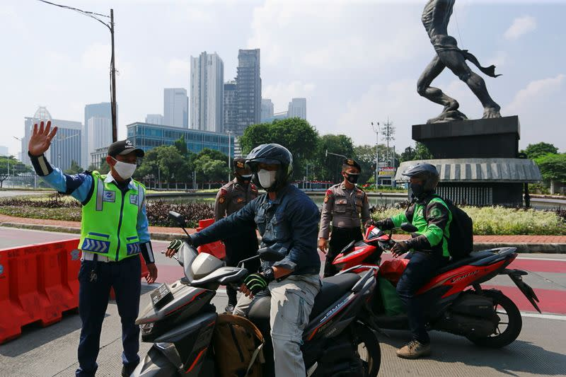 Officials stop motorbikes while enforcing large-scale social restrictions to prevent the spread of coronavirus disease (COVID-19)