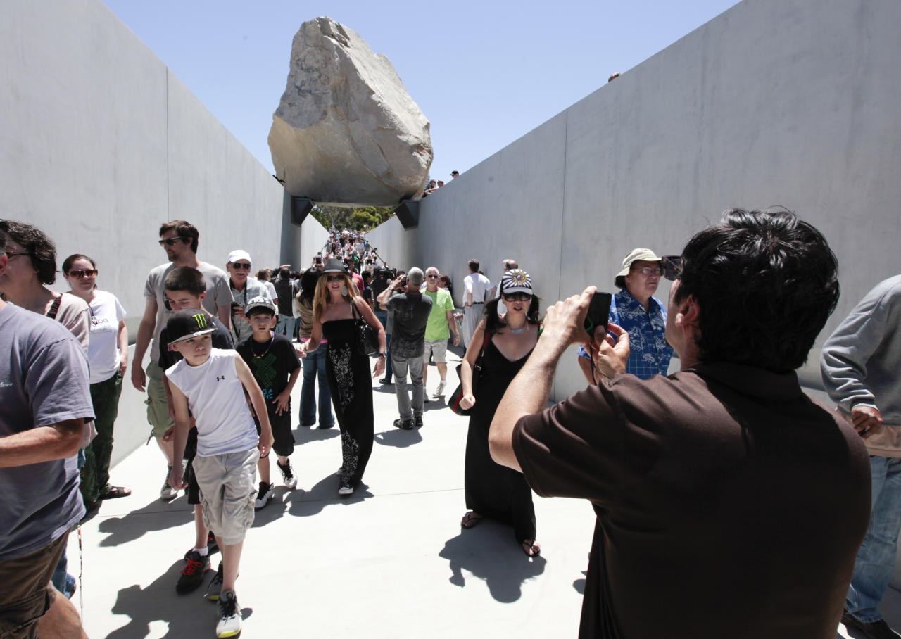 "Visitors view Michael Heizer's ""Levitated Mass"" at the Los Angeles County Museum of Art in Los Angeles, on Sunday June 24,2012. Thousands showed up as the gigantic work was unveiled on the museum's rear lawn, where it is intended to remain forever. (AP Photo/Richard Vogel)"