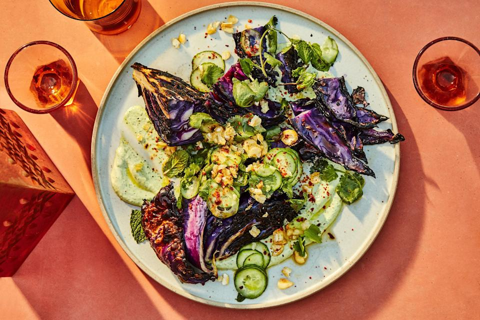 """Deeply charred cabbage wedges give this zesty, herb-laced salad a lot of personality. Corn nuts give it welcome crunch. <a href=""""https://www.epicurious.com/recipes/food/views/grilled-charred-cabbage-with-goat-cheese-raita-and-cucumbers?mbid=synd_yahoo_rss"""" rel=""""nofollow noopener"""" target=""""_blank"""" data-ylk=""""slk:See recipe."""" class=""""link rapid-noclick-resp"""">See recipe.</a>"""