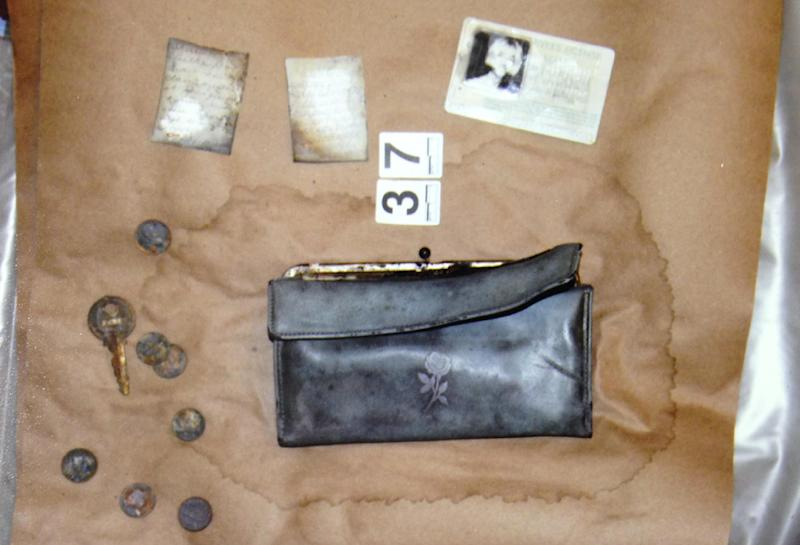 In this undated photo provided by the South Dakota Attorney Generals Office, Cheryl Miller's driver's license, purse and other belongings are seen. Two South Dakota girls on their way to an end-of-school-year party at a gravel pit in May 1971 drove off a country road into a creek and remained hidden until last fall when a drought brought their car into view, authorities said Tuesday, April 15, 2014. State and local officials held a news conference Tuesday afternoon confirming that the 1960 Studebaker unearthed in September included the remains of Cheryl Miller and Pamella Jackson, both 17-year-olds who attended Vermillion High School. (AP Photo/South Dakota Attorney Generals Office)