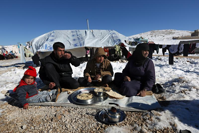 Syrian refugees eat their lunch outside their tent at a refugee camp in the eastern Lebanese border town of Arsal, Lebanon, Sunday, Dec. 15, 2013. Tens of thousands of impoverished Syrian refugees living in tents, shacks and unfinished buildings throughout Lebanon face a miserable winter as aid organizations scramble to meet their needs, constantly overwhelmed by ever-more Syrians fleeing their country's war. Charities have already distributed blankets, mattresses, kerosene heaters, winter clothes and coupons for fuel ahead of the region's unprecedented storm this week that blanketed parts of Lebanon, the Palestinian Territories, Turkey, Israel and even Egypt's deserts with snow, amid icy and rainy winds. (AP Photo/Bilal Hussein)