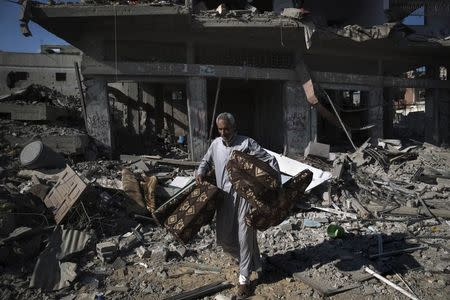 A Palestinian man salvages belongings from damaged buildings in the Shejaia neighbourhood, which witnesses said was heavily hit by Israeli shelling and air strikes during an Israeli offensive, in Gaza City July 27, 2014. REUTERS/Finbarr O'Reilly