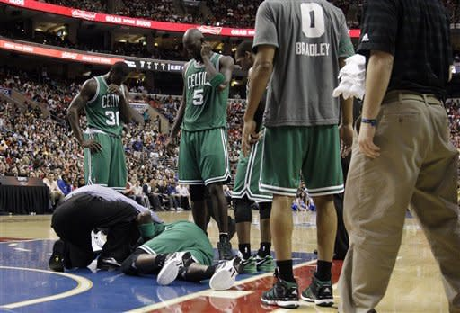 Boston Celtics players gather around an injured Mickael Pietrus, of France, in the first half of an NBA basketball game against the Philadelphia 76ers, Friday, March 23, 2012, in Philadelphia. (AP Photo/Matt Slocum)