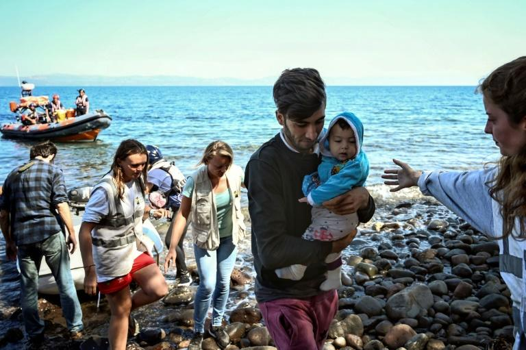 Migrants with a child, helped by rescuers, arrive on the Greek island of Lesbos after crossing the Aegean Sea from Turkey