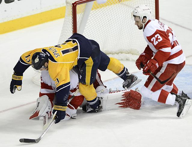 Nashville Predators forward Nick Spaling (13) falls over Detroit Red Wings goalie Jimmy Howard after stopping a shot by Spaling while being defended by Red Wings defenseman Brian Lashoff (23) in the second period of an NHL hockey game on Monday, Dec. 30, 2013, in Nashville, Tenn. (AP Photo/Mark Zaleski)