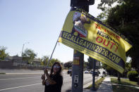 A supporter of the California recall of Gov. Gavin Newsom holds a sign outside of a debate by Republican gubernatorial candidates at the Richard Nixon Presidential Library Wednesday, Aug. 4, 2021, in Yorba Linda, Calif. Newsom faces a Sept. 14 recall election that could remove him from office. (AP Photo/Marcio Jose Sanchez)