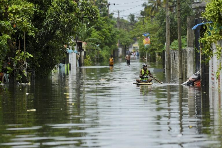 A man uses a makeshift raft to negotiate floodwaters after heavy monsoon rains in Kelaniya