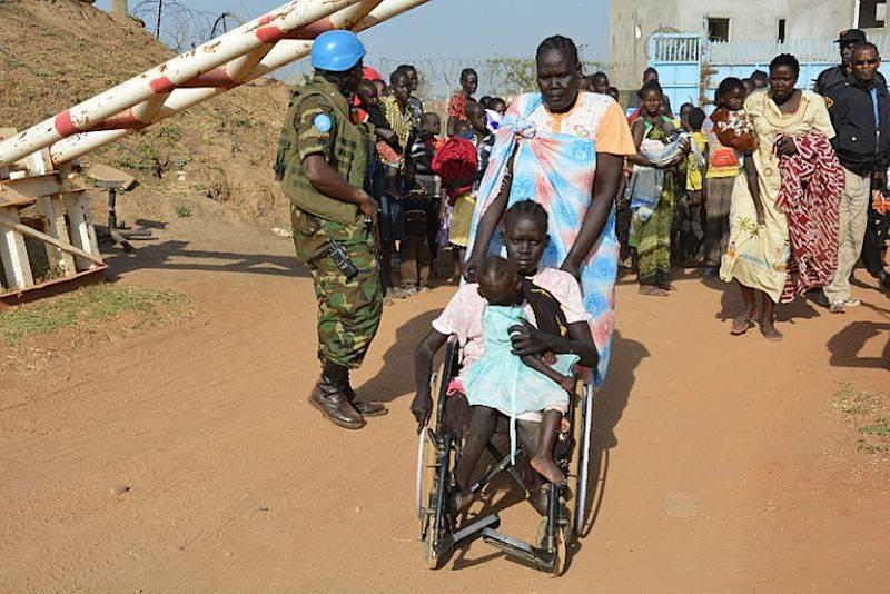 """In this handout image provided by the United Nations Mission in South Sudan, taken on Tuesday, Dec. 17, 2013, a United Nation soldier stands guard as civilians arrive at the UNMISS compound adjacent to Juba International Airport to take refuge. Sporadic gunfire rang out in the capital, Juba, overnight as the military """"cleared out remnants"""" of a faction of soldiers accused of mounting a coup attempt, the country's foreign minister said Tuesday amid an ongoing hunt for the former deputy president who is accused of leading the failed plot. (AP Photo/UNMISS/Rolla Hinedi)"""