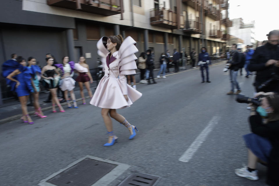 A young model shows a creation by fashion student Nora Bourelly on a street outside Valentino women's Spring-Summer 2021 fashion show location, in Milan, Italy, Sunday, Sept. 27, 2020. (AP Photo/Luca Bruno).