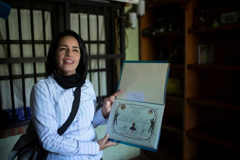 "Ismaira Figueroa, a sniper for the Bolivarian militia in Venezuela, keeps a folder with her diplomas, including a sheet of paper with six holes in it that confirmed her graduation as an ""expert marksman"" in 2016"