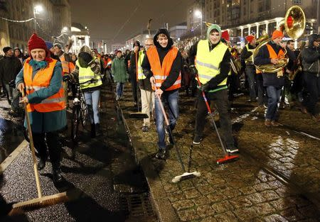 Participants of an alternative rally use brooms as they protest against a demonstration called by anti-immigration group PEGIDA in Dresden