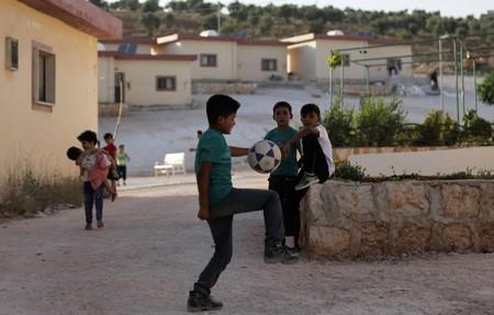 FILE PHOTO: Children play near apartments built for people who had lost family members during the war, in Idlib countryside