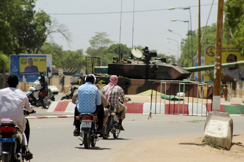 People drive past a Chad army tank near the presidential palace, in N'djamena