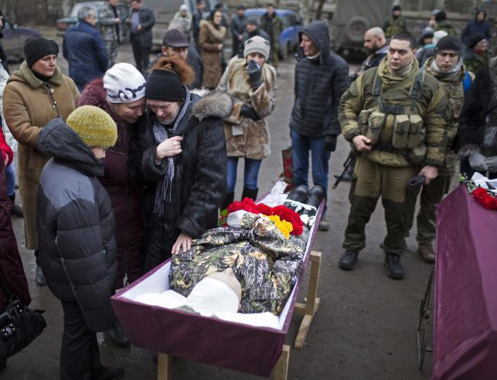FILE - In this Feb. 5, 2015, file photo, relatives of a pro-Russian rebel fighter killed during fighting against Ukrainian government forces, mourn during his funeral in Vuhlehirsk, Donetsk region, eastern Ukraine, after the separatists recently burst through government lines in Vuhlehirsk. Tensions have risen in the conflict in eastern Ukraine, with growing violations of a cease-fire and a massive Russian military buildup on its side of the border. Ukraine and the West have become increasingly worried about the presence of more Russian troops and urged Moscow to pull them back. (AP Photo/Vadim Braydov, File)