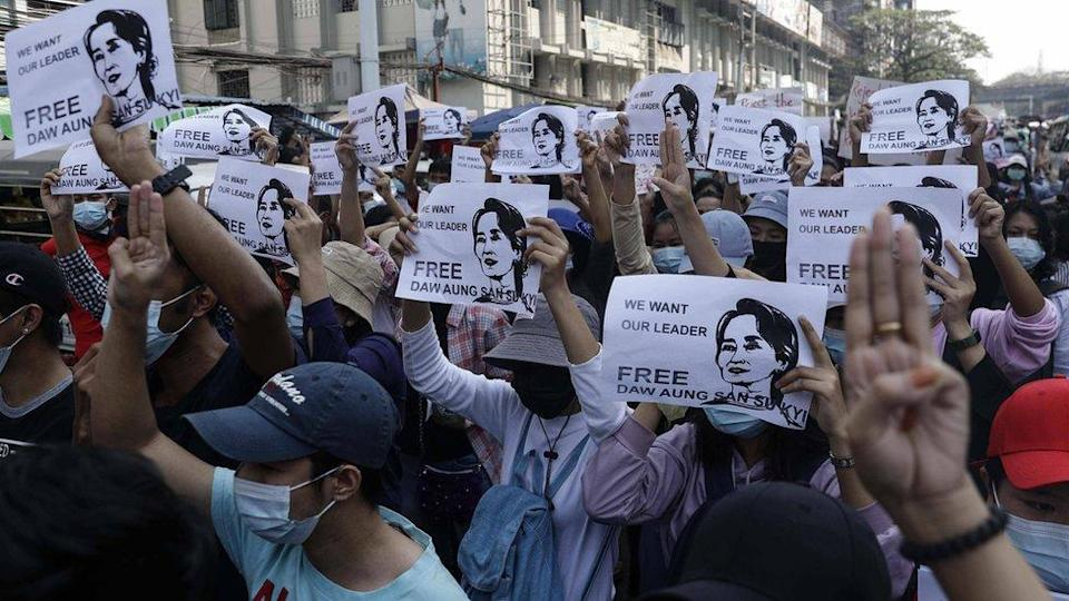 Demonstrators hold placards showing the image of detained Myanmar leader Aung San Suu Kyi in Yangon