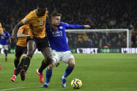 Wolverhampton Wanderers' Willy Boly, left, fights for the ball with Leicester's Harvey Barnes during the English Premier League soccer match between Wolverhampton Wanderers and Leicester City at the Molineux Stadium in Wolverhampton, England, Friday, Feb. 14, 2020. (AP Photo/Rui Vieira)