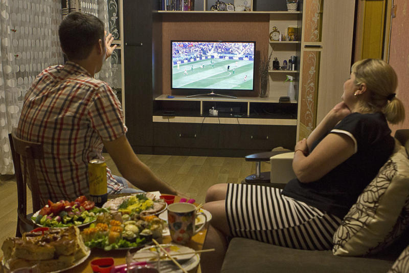 Anatolii and Julia in front of the TV watching the game.
